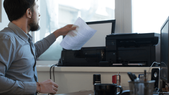Man holding piece of paper to scan with a printer